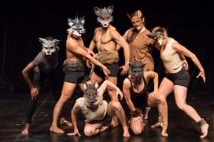 Group of Dancers from Sacred Trout performances standing and crouching, wearing animal masks and striking a powerful pose