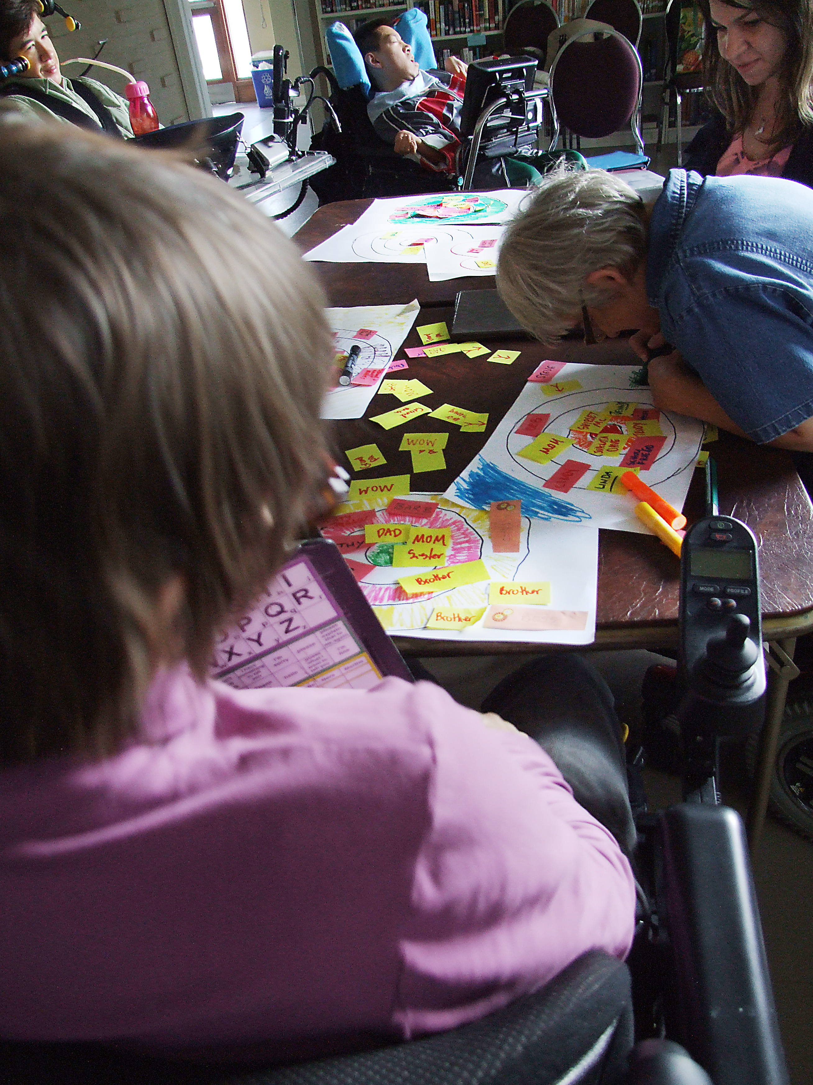 woman in blue shirt sitting in wheelchair leans over table to draw on paper
