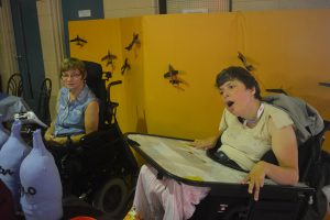 Woman in blue in wheelchair sits with woman in yellow in wheelchair