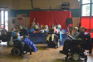 Group of five wheelchair users in front of table full of items