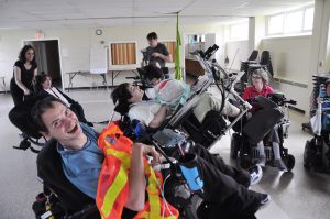 man in wheelchair holding safety vest sits with other wheelchair users and smiles