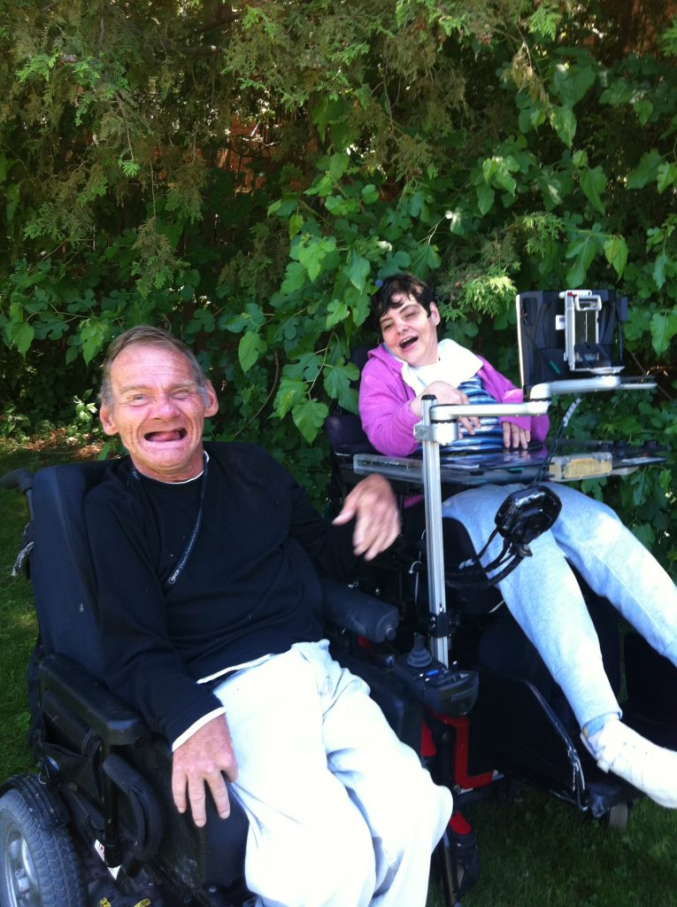 Man in black sweater in wheelchair sits and smiles with woman in pink jacket in wheelchair
