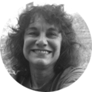 Black and white headhsot of woman with curly hair smiling
