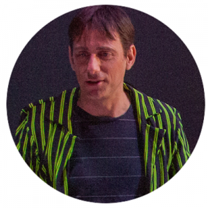 Man in striped green shirt looks down and smiles