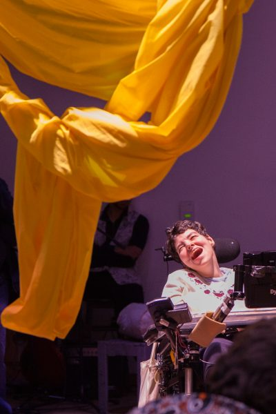 Woman wearing white shirt in wheelchair looks up at yellow fabric hanging off ceiling and smiles