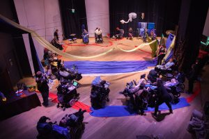 group of wheelchair users sit in circle around long piece of blue fabric on stage