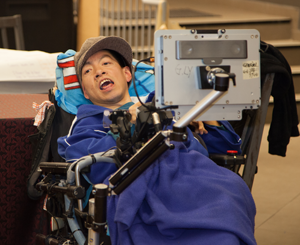 Man wearing blue sweater and brown cap sits back in wheelchair and smiles