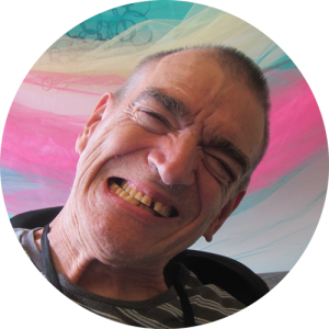 Man in striped grey shirt sitting in wheelchair tilts head and smiles