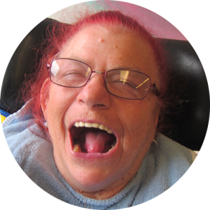Woman with glasses and pink hair sitting in a wheelchair laughs