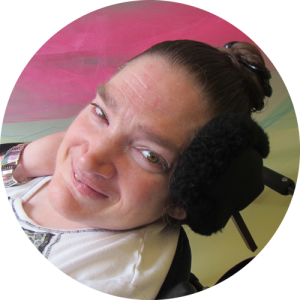 Woman with hair in a bun sitting in a wheelchair rests her head