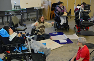 Woman sits by pieces of paper and speaks to group of four wheelchair users