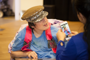 Woman in blue takes picture of man in blue shirt and sparkly brown cap sitting in wheelchair