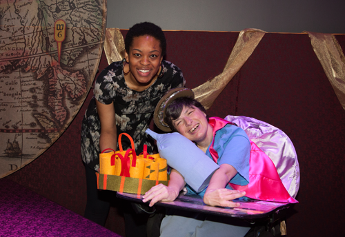 woman in patterned shirt smiles with woman in pink jacket stting in wheelchair holding stage props