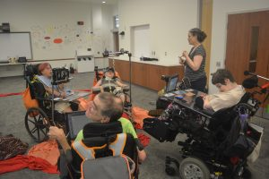 Group of four wheelchair users and woman discuss in a circle with fabric on floor