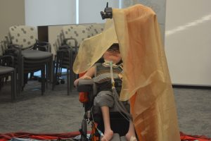 Young boy wearing glasses sitting in wheelchair smiles as he is covered in fabric