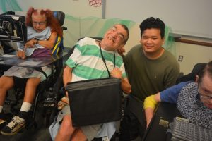Man in green and white striped shirt sitting in wheelchair poses with man in green shirt