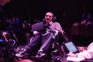 Man wearing track pants and sneakers sitting in wheelchair on stage looks up and smiles