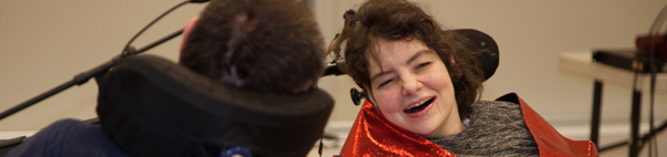 Woman wearing red sitting in wheelchair talks and laughs with man in wheelchair