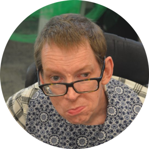 Man wearing glasses and a patterned scarf sits in a wheelchair