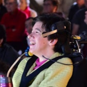 Woman wearing yellow and headset sitting in wheelchair watches and laughs
