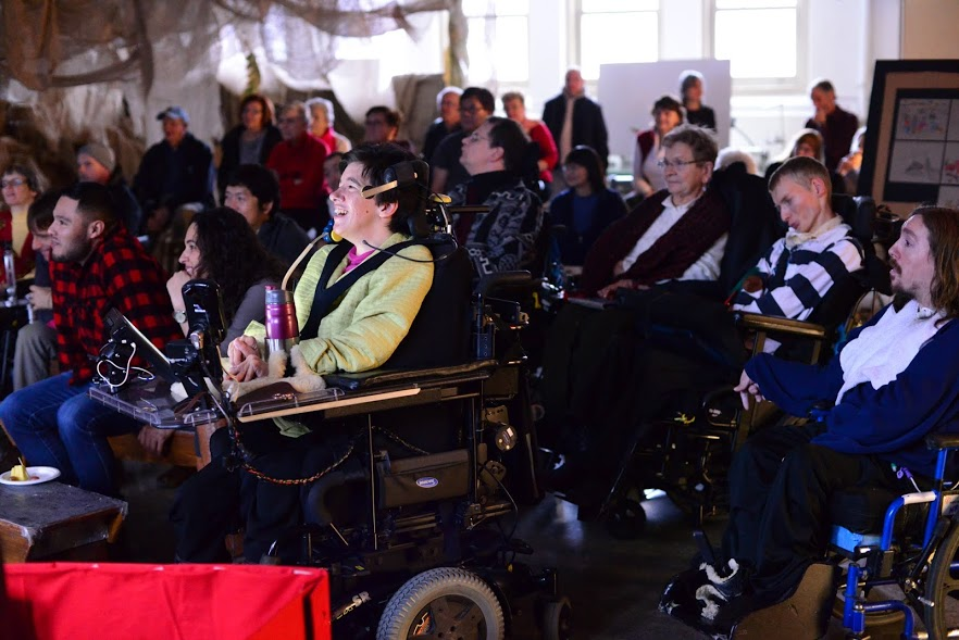 Group of wheelchair users on stage with fabric watching a performance